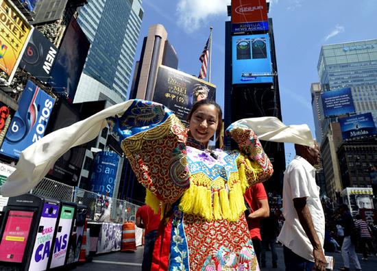 An artist promotes Peking Opera at Times Square in New York City. China's national image in the international community has continued to improve in recent years, according to a report released in Beijing on Sept 15. (WANG LEI/XINHUA)