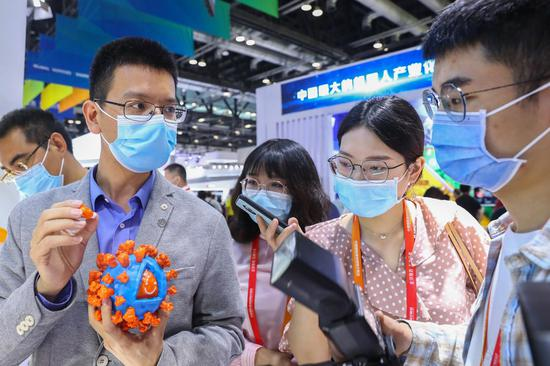 An exhibitor shows a 3D model of inactivated COVID-19 vaccine antigen to visitors at the booth of SINOVAC at the 2020 China International Fair for Trade in Services (CIFTIS) in Beijing, capital of China, Sept. 5, 2020. (Xinhua/Zhang Yuwei)