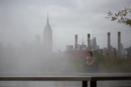 A person wearing a face mask stands in Domino Park during the COVID-19 pandemic in New York, the United States, Sept. 13, 2020. (Photo by Michael Nagle/Xinhua)