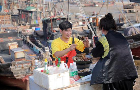 A live streamer (L) sells seafood products via internet at Haitou Town in Lianyungang, east China's Jiangsu Province, June 10, 2020. (Xinhua/Li Yuze)