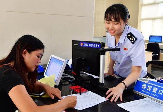 A staff member of tax service (R) helps a financial staff of a company to fill in the application for her company's tax cuts and fee reductions in Fuzhou, capital of southeast China's Fujian Province, Aug. 21, 2019. (Xinhua/Wei Peiquan)