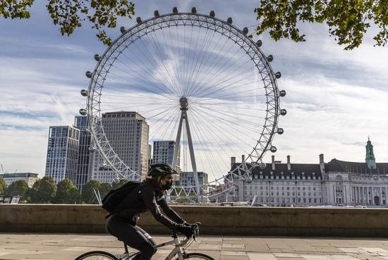 A woman wearing a face mask cycles past the London Eye in London, Britain, on Sept. 28, 2020. (Xinhua/Han Yan)