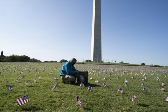 A man is seen with a picture of his family member who died from COVID-19 among U.S. national flags representing the 200,000 lives lost to COVID-19 in the United States placed on the National Mall in Washington, D.C., the United States, on Sept. 22, 2020. (Xinhua/Liu Jie)