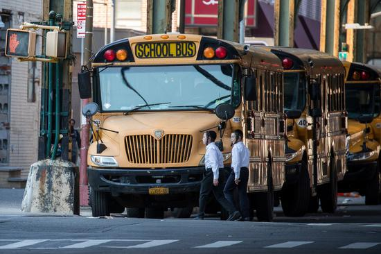 Children walk past school buses in the Borough Park neighborhood in the Brooklyn borough of New York, the United States, Oct. 4, 2020. (Photo by Michael Nagle/Xinhua)
