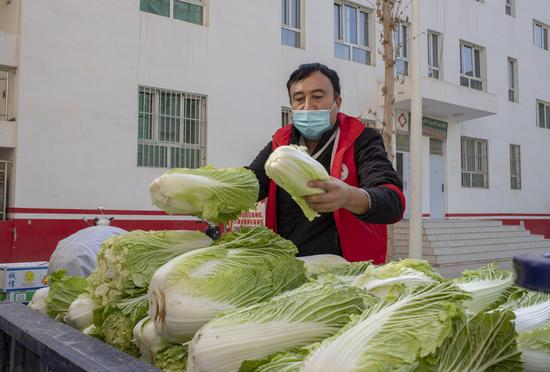 A volunteer prepares to deliver vegetable to a community in Tokzak Township, Shufu County of Kashgar Prefecture, northwest China's Xinjiang Uygur Autonomous Region, Oct. 26, 2020. (Xinhua/Hu Huhu)
