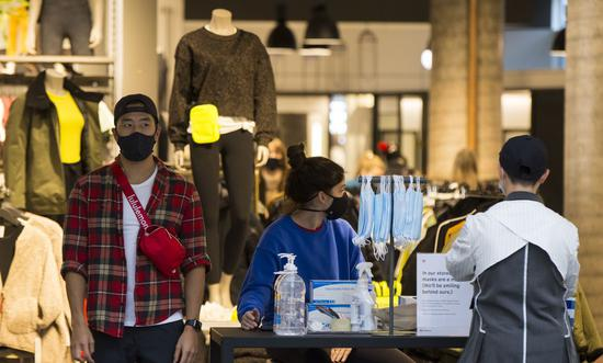 Personal protective equipment for customers are placed at the entrance of a clothing store in Toronto, Canada, on Oct. 27, 2020. (Photo by Zou Zheng/Xinhua)