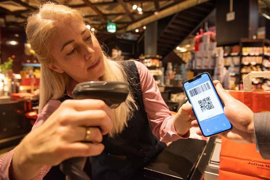 A staff member scans a QR code from a customer's Alipay app at Julius Meinl, a coffee shop in Vienna, Austria, on Jan. 9, 2020.(Xinhua/Guo Chen)