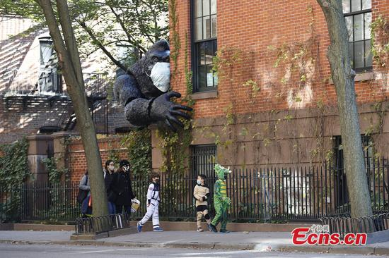 Children wearing costumes walk in Brooklyn, New York, United States, on Oct. 31, 2020. Due to the ongoing COVID-19 pandemic, New Yorkers maintained social distancing while celebrating this year's Halloween. (Photo: China News Service/Wang Fan)