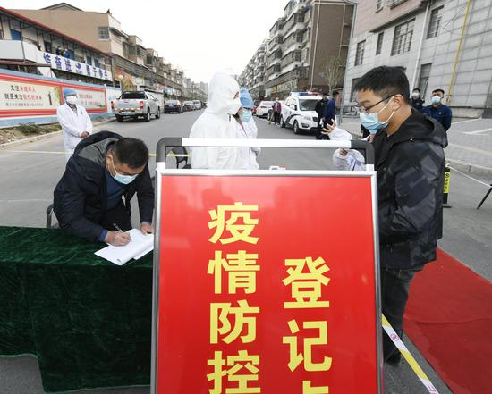 Community workers check information at Zhangyang residential community in Yingshang county, Fuyang, Anhui province, on Tuesday. (GUO HAIYANG/FOR CHINA DAILY)