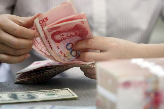 A worker counts Chinese currency renminbi at a bank in Linyi, East China's Shandong province. (Photo/Xinhua)