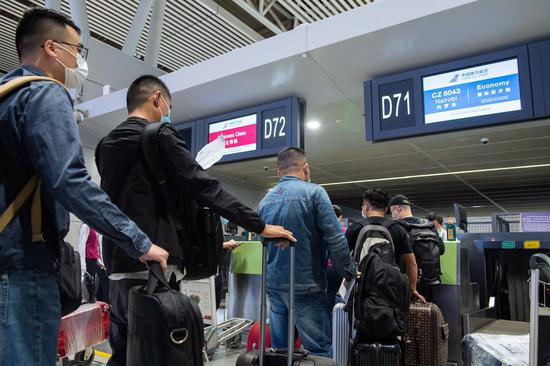 Passengers queue to check in at the Changsha Huanghua International Airport in Changsha, capital of central China's Hunan Province, Oct. 13, 2020. (Xinhua/Chen Sihan)