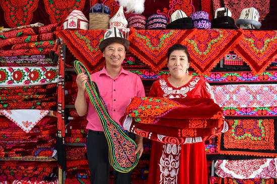 A couple display embroidery works at a handicraft making cooperative in Aketao County of northwest China's Xinjiang Uygur Autonomous Region, Sept. 20, 2020. (Xinhua/Gao Han)