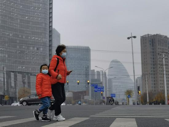 A woman and child walk in the smog on a street in Beijing's Wangjing area on Nov. 16, 2020. (Photo by Wang Jing/chinadaily.com.cn)