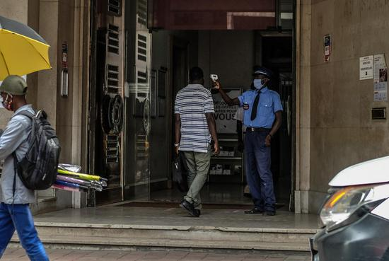 A security guard takes the body temperature of a client at a bank in central Dakar, Senegal, on July 21, 2020. (Photo by Eddy Peters/Xinhua)