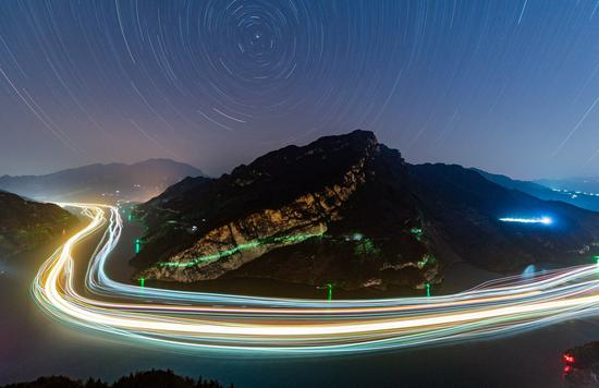 This long-time exposure photo shows the night scene of ships sailing in a section of the Xiling Gorge along the Yangtze River in Zigui County, central China's Hubei Province, Nov. 13, 2020. (Photo by Zheng Jiayu/Xinhua)