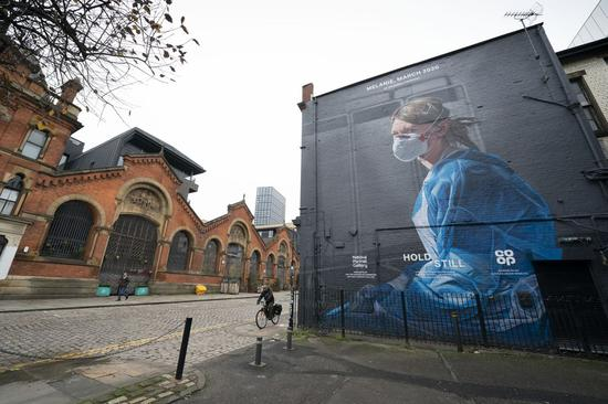 People pass by a recently painted mural of a nurse in Manchester, Britain, Nov. 5, 2020. (Photo by Jon Super/Xinhua)