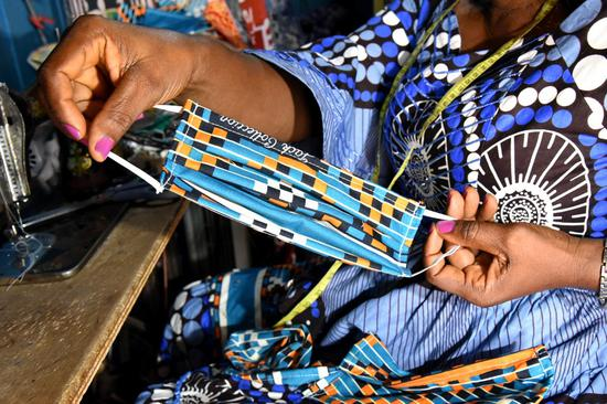 Angeline Toungsi, a Cameroonian tailor, sews cloth face masks at her workshop in Yaounde, Cameroon on April 9, 2020. (Xinhua/Jean Pierre Kepseu)