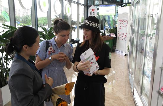 A shop staff member introduces new biodegradable plastic products to an English teacher working in Haikou, Hainan province. [Photo by Ma Zhiping/China Daily]