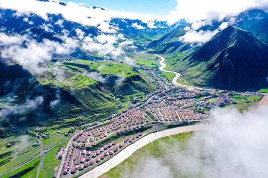 Aerial photo taken on June 14, 2020 shows a relocated area by the Gaqu River in Chido Township of Dengqen County in Qamdo, southwest China's Tibet Autonomous Region. Qadom City has witnessed a total of 194,600 residents, 38,400 households, 1,127 villages and 11 counties get rid of poverty thanks to the poverty alleviation efforts. (Xinhua/Tian Jinwen)