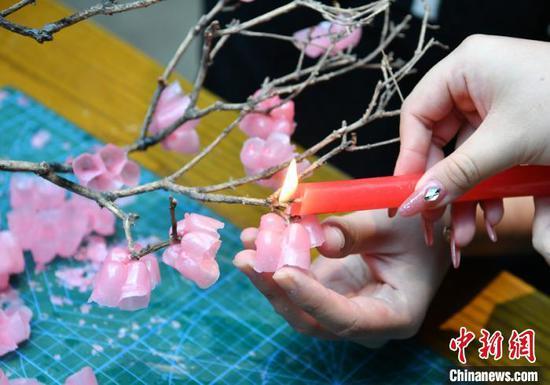 College student creates vivid plum flowers with wax
