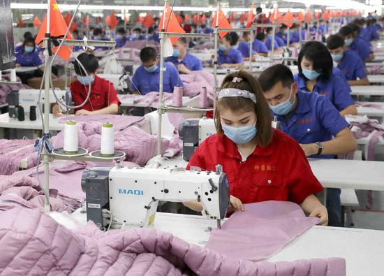 Workers make down-filled coats at a factory in Jiashi county, Xinjiang Uygur autonomous region. (WANG ZHUANGFEI/CHINA DAILY)