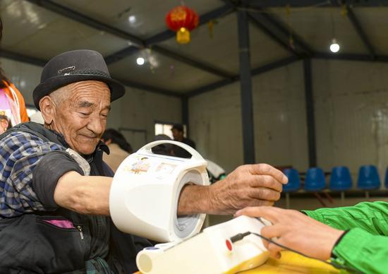 A villager has his blood pressure measured at the clinic of Yaragzi Village in Xihxu Township in Yecheng County, northwest China's Xinjiang Uygur Autonomous Region, May 2, 2020. (Xinhua/Hu Huhu)