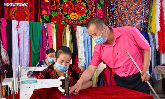 A man guides a staff member in embroidery works at a handicraft making cooperative in Aketao County of northwest China's Xinjiang Uygur Autonomous Region, Sept. 20, 2020.  (Xinhua/Gao Han)