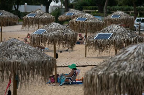 2020年7月21日拍摄的照片显示了在遮阳伞上的太阳能电池板,位于希腊南部雅典瓦里-沃拉-沃拉格梅尼市政府附近的一个开放的公共海滩上。 (照片由Lefteris Partalis /新华社拍摄)