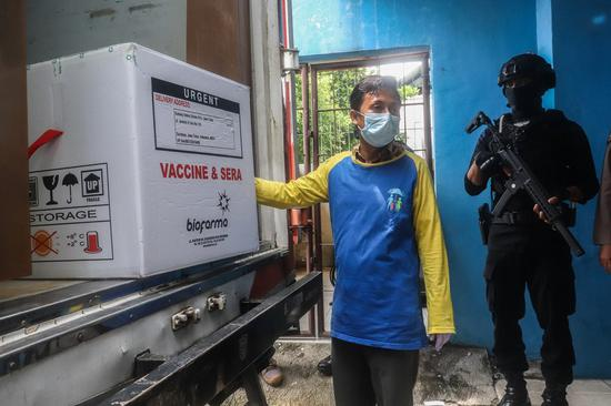 A health worker unloads a box containing COVID-19 vaccines made by the Chinese biopharmaceutical company Sinovac Biotech in Surabaya, East Java, Indonesia, Jan. 4, 2021. (Photo by Surya Betha/Xinhua)