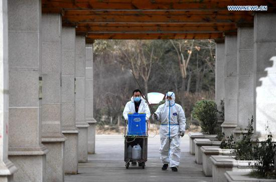Staff members spray disinfectant at a community which was classified as a medium-risk area for COVID-19, in Yuhua district of Shijiazhuang, North China's Hebei province, Jan 12, 2021. (Photo/Xinhua)