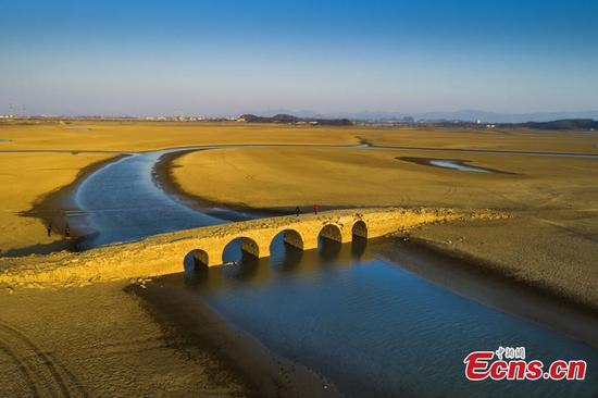 Ancient stone arch bridge emerges from drying Poyang Lake
