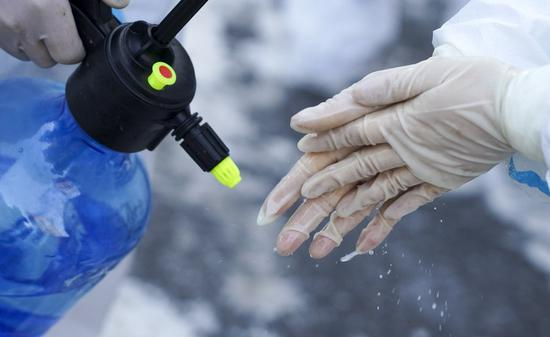 A worker disinfects hands at a community in Dongchang District of Tonghua City, northeast China's Jilin Province, Jan. 17, 2021. (Xinhua/Xu Chang)