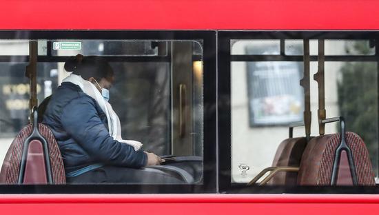 A woman wearing a face mask is seen in a bus in London, Britain, Jan. 8, 2021. (Xinhua/Han Yan)