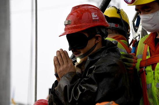 A trapped miner expresses his gratitude after being lifted from a gold mine in Qixia City, east China's Shandong Province, on Jan. 24, 2021. (Xinhua/Chen Hao)