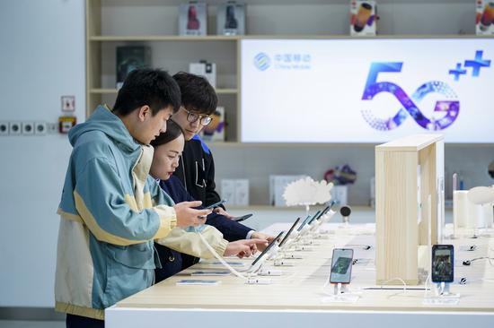 消费者在2019年10月31日于中国首都北京的中国移动北京分公司营业厅体验5G手机。(新华社/沉伯涵)