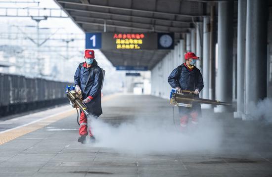Volunteers disinfect the platform of Liupanshui Railway Station in Liupanshui, southwest China's Guizhou Province, Jan. 28, 2021. (Xinhua/Tao Liang)