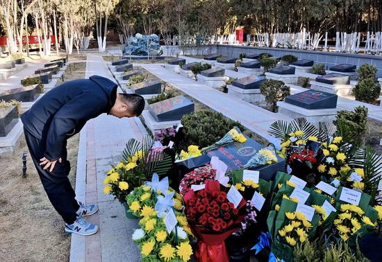 Guo Huaide pays respects in Lanzhou, Gansu province, on Saturday to Chen Hongjun, one of the four martyrs who died during the border clash with India in June. Chen was a college classmate of Guo. (Photo: Wei Dezhan/For China Daily)