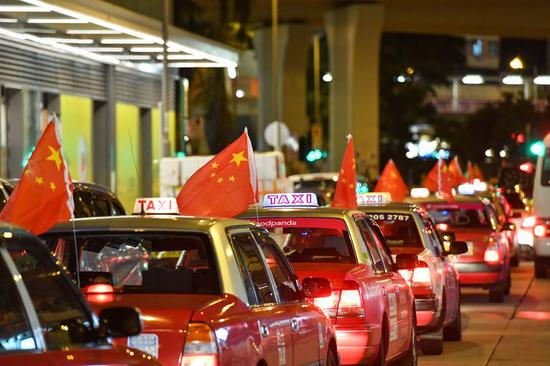Taxis hanging Chinese national flags participate in a peace rally in Hong Kong, south China, Aug. 23, 2019. (Xinhua/Liu Dawei)