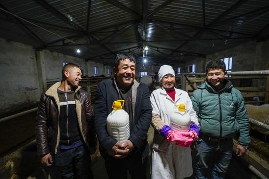 Ghulam Tuniyaz (2nd L) and his family show just-collected donkey milk at Jiayi Nagute Village, Koxtag Township, Pishan County, in Hotan of northwest China's Xinjiang Uygur Autonomous Region, Feb. 4, 2021. (Xinhua/Zhao Ge)