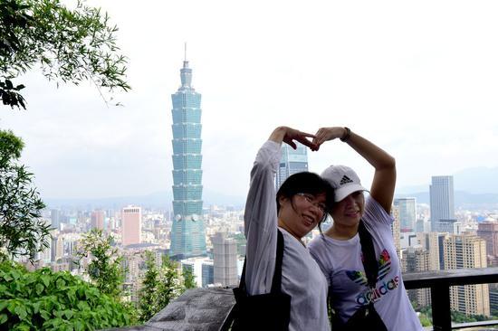 Tourists pose for a photo at Xiangshan Mountain in Taipei, southeast China's Taiwan, July 21, 2019. (Xinhua/Zhu Xiang)