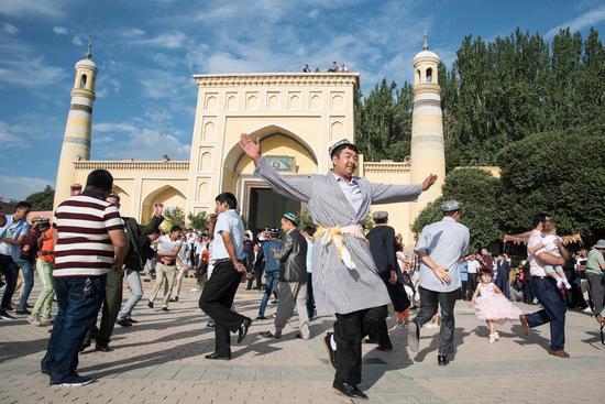 Muslims dance in front of the Id Kah Mosque in Kashgar, northwest China's Xinjiang Uygur Autonomous Region, July 6, 2016. (Xinhua/Bu Duomen)