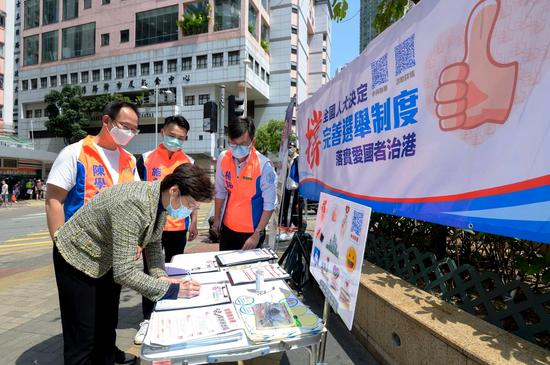 Chief Executive of the Hong Kong Special Administrative Region Carrie Lam Cheng Yuet-ngor signs her name to a petition in Hong Kong on Monday in support of the National People's Congress' decision on improving the electoral system of the HKSAR. (CHINA DAILY)