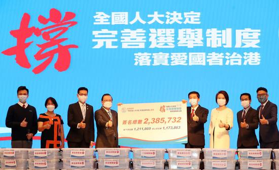 Tam Yiu-chung (4th L), one of the conveners, hands over a petition to Luo Huining (4th R), director of the Liaison Office of the Central People's Government in the Hong Kong Special Administrative Region (HKSAR), in Hong Kong, south China, March 24, 2021. (Xinhua/Li Gang)