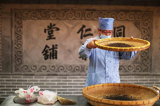 A pharmacist processes a traditional Chinese medicine at a Beijing Tongrentang Group Co Ltd's factory in Beijing.(Photo/China Daily)