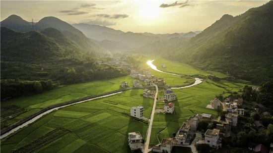 The sun sets on Jinxing village in Chengbu Miao ethnic autonomous county, Hunan province. Chengbu was removed from the list of impoverished counties at the beginning of last year, having become a booming tourism and agricultural center. (Photo provided to China Daily)