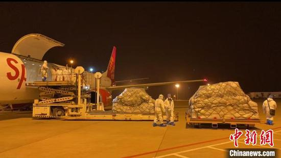 Workers load goods on a cargo plane departed from Wuhan in central China for Delhi, India, March 30, 2021.