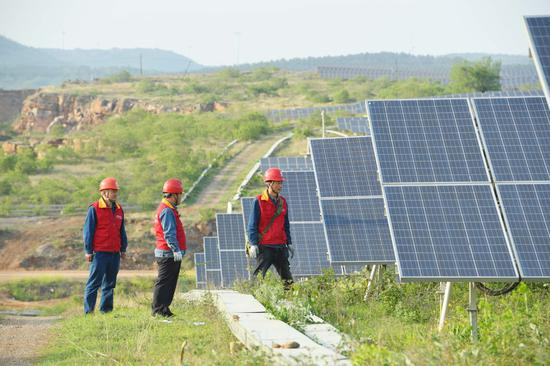State Grid employees inspect photovoltaic panels in Chuzhou, Anhui province. SONG WEIXING/FOR CHINA DAILY