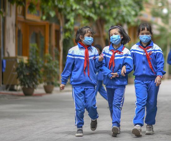 儿童在街上走在街上,在古城克什古城的一个景区,西北新疆尼古自治区,2020年5月16日。(新华社/赵格)