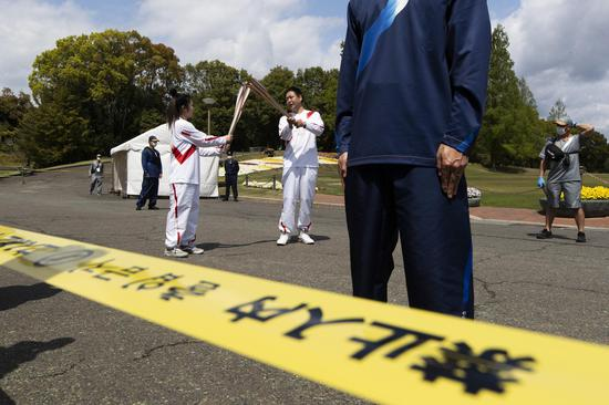 Tokyo Olympic torch relay: runners cross nearly empty park