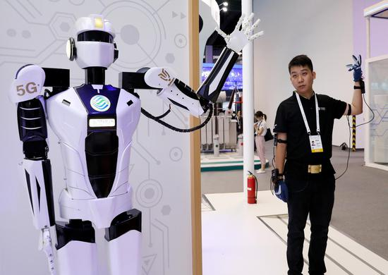 A staff member demonstrates 5G-based remote control of a robot during the 2019 World Artificial Intelligence Conference in Shanghai, Aug. 29, 2019. (Xinhua/Fang Zhe)